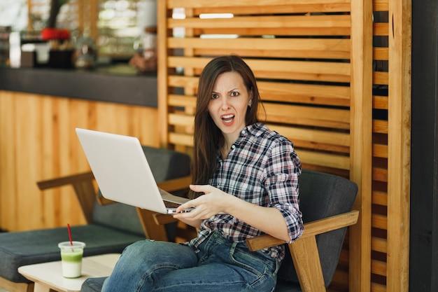 Enojado gritando triste niña molesta en el café de madera de la cafetería de la calle al aire libre sentado con una computadora portátil moderna, molestar el problema durante el tiempo libre. oficina móvil