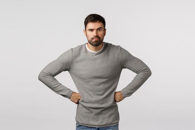 Enojado y gruñón, disgustado hombre estricto o serio con barba, usa suéter gris, toma las manos en la cintura en una postura exigente y decepcionada, frunce el ceño y hace una mueca molesto, regaña a alguien