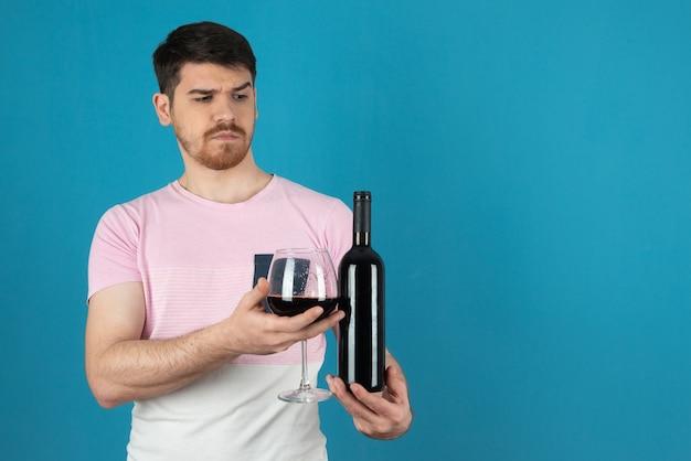 Enojado guapo y sosteniendo una copa de vino y una botella en un azul.