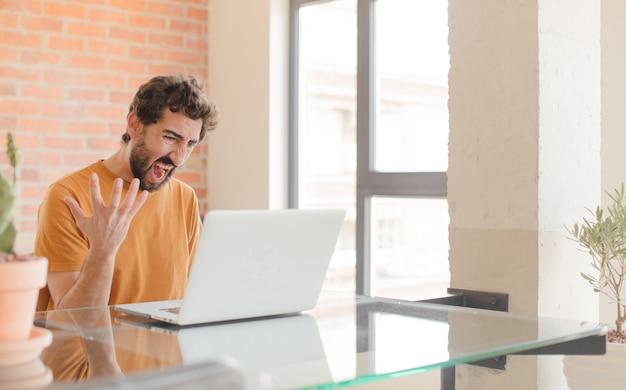 Enojado, joven, con, un, computador portatil, en, un, escritorio