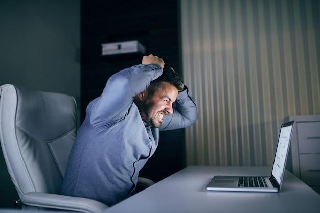 Enojado joven empleado barbudo caucásico mirando portátil mientras estaba sentado en la oficina a altas horas de la noche.