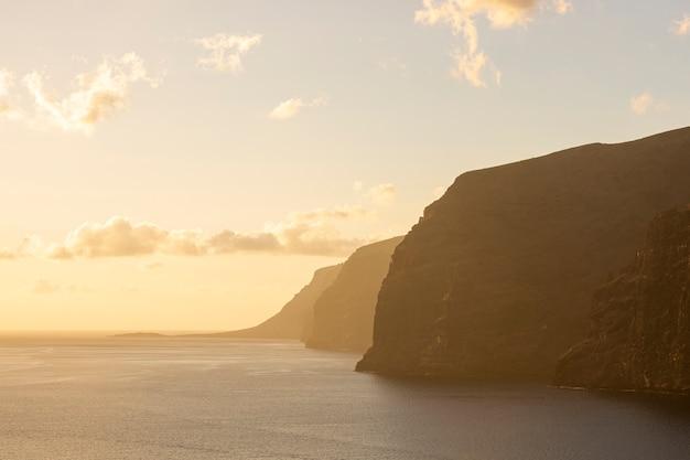 Enorme acantilado en la puesta de sol junto al mar
