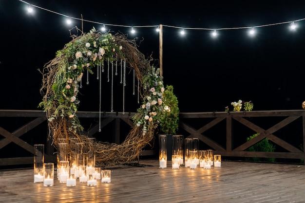 Enorme círculo decorativo hecho de sauce, vegetación y rosas de color naranja pálido con velas encendidas