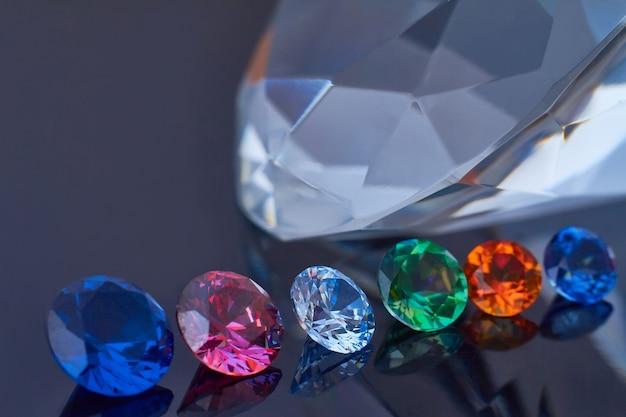 Enorme diamante y varios cristales elegantes en una superficie de espejo negro profundo, brillan y brillan