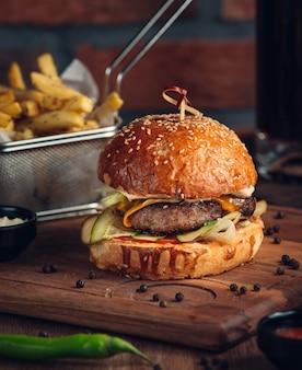 Enorme hamburguesa con carne frita y verduras