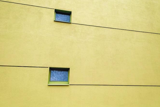 Enorme pared amarilla en un edificio moderno con dos ventanas y líneas. reflejos en ventanas. copia espacio