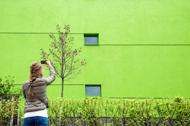 Enorme pared en un edificio moderno con dos ventanas y líneas. reflejos en ventanas. copia espacio chica haciendo fotos en el teléfono