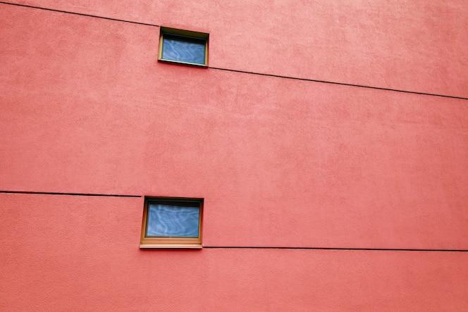 Enorme pared roja en un edificio moderno con dos ventanas y líneas. reflejos en ventanas. copia espacio