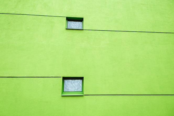 Enorme pared verde en edificio moderno con dos ventanas y líneas. reflejos en ventanas. copia espacio