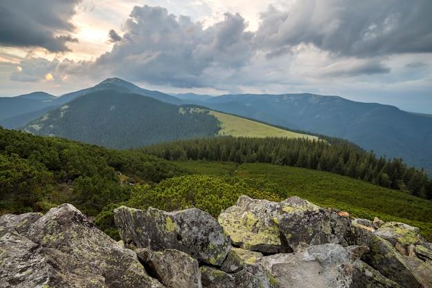 Enormes rocas de roca en el valle verde con arbustos de arándanos en montañas leñosas distantes.