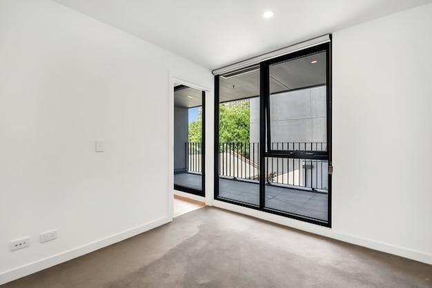 Enormes ventanas y puertas de un balcón capturadas desde la habitación.