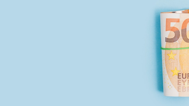 Enrollado billete de cincuenta euros atado con goma sobre fondo azul