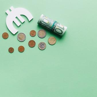 Enrollado billete de cien euros con símbolo y monedas sobre fondo verde