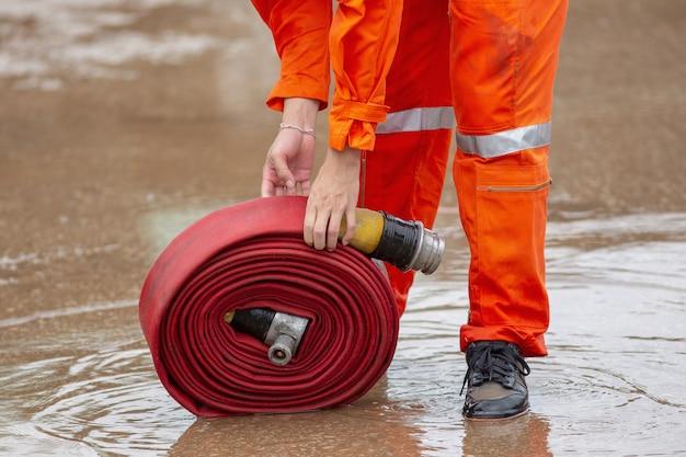 Enrollado en una manguera de bomberos roja, extintores de extinción de incendios listos para usar