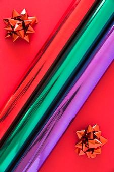 Enrollado papel brillo con lazo sobre fondo rojo