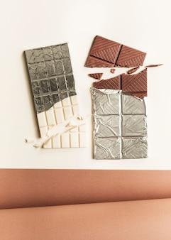 Enrollado papel de tarjeta con dos barras de chocolate contra el fondo blanco