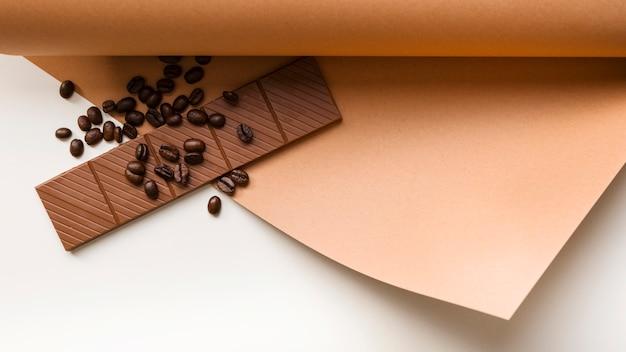 Enrollado papel de tarjeta con granos de café tostados y barra de chocolate sobre fondo blanco