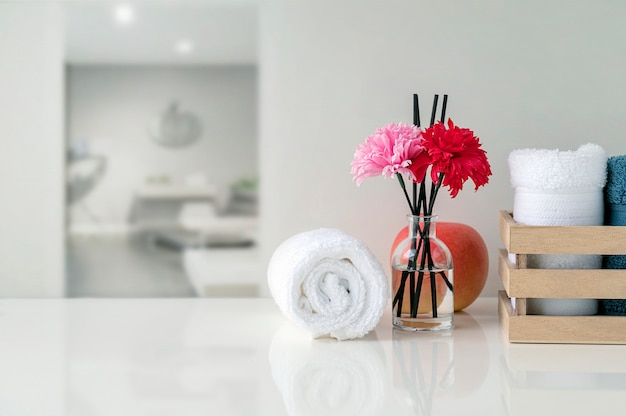 Enrolle para arriba de las toallas blancas en la tabla blanca con el espacio de la copia en fondo borroso de la sala de estar.