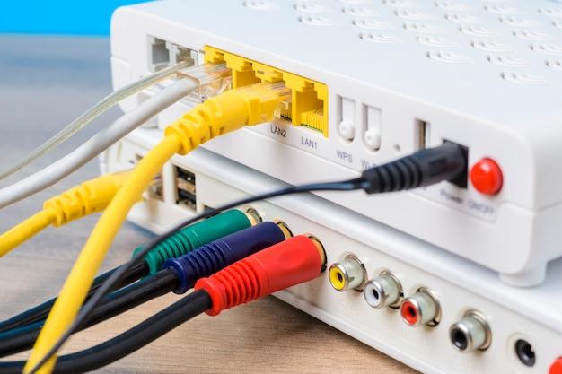 Enrutador inalámbrico doméstico con cables ethernet enchufados sobre fondo azul