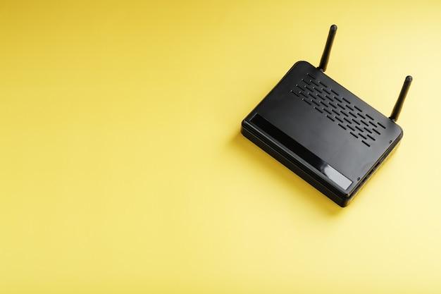 Enrutador wi-fi negro sobre un fondo amarillo con espacio libre. aislar, vista superior. en línea