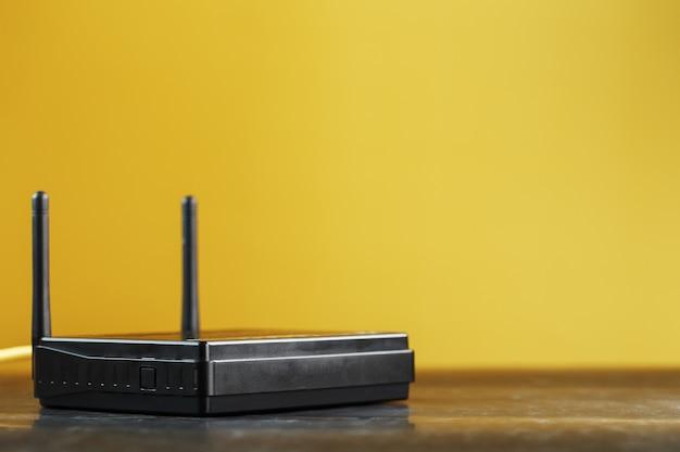 Enrutador wi-fi negro sobre un fondo amarillo con espacio libre.