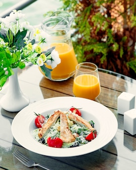 Ensalada aesar con pollo y un vaso de jugo de naranja