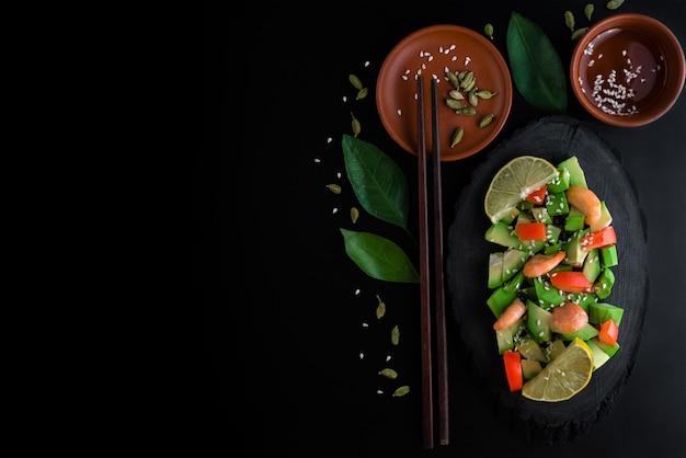 Ensalada de aguacate saludable vegetariana brillante con gambas, tomate y aceite de oliva limón sobre negro, deliciosa comida en la oscuridad
