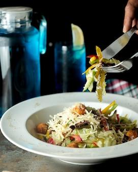 Ensalada de albóndigas con lechuga pimientos morrones tomate parmesano pepinillos en vinagre