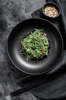 Ensalada de algas con semillas de sésamo en un plato con palillos. vista superior