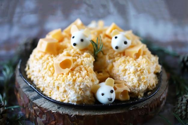 Ensalada de año nuevo 2020. ensalada de ratón en queso con piña y queso. decoraciones en forma de ratones huevo.