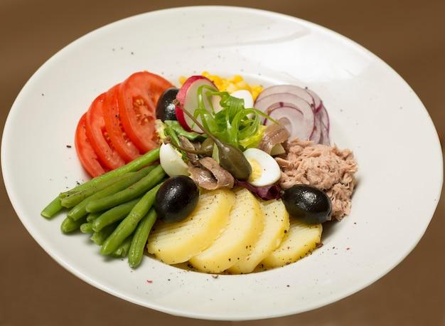 Ensalada de atún con verduras, colocada en un plato blanco, fondo marrón