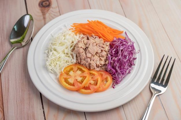 Ensalada de atún con zanahorias, tomates, repollo en un plato blanco sobre un piso de madera.