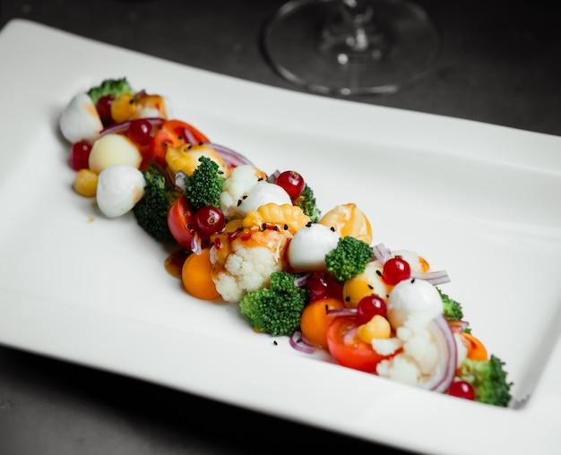 Ensalada con bayas, hierbas, tomates cherry y bolas de mozarella.