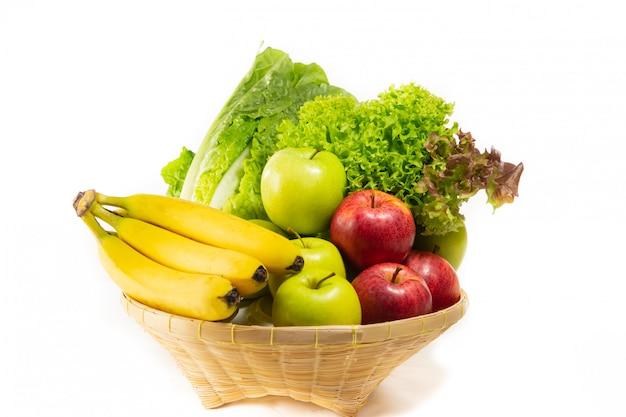 Ensalada bio-orgánica de verduras, manzanas, plátanos en una cesta.