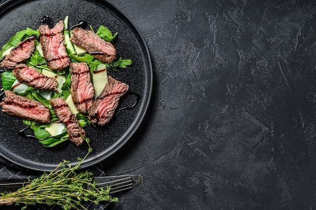 Ensalada de bistec con espinacas, rúcula y filete marmolado de ternera en rodajas