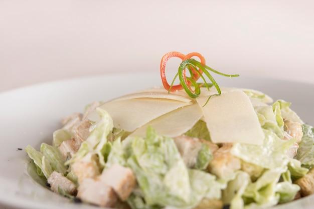 Ensalada caeser con filete de pollo, plato blanco, fondo marrón