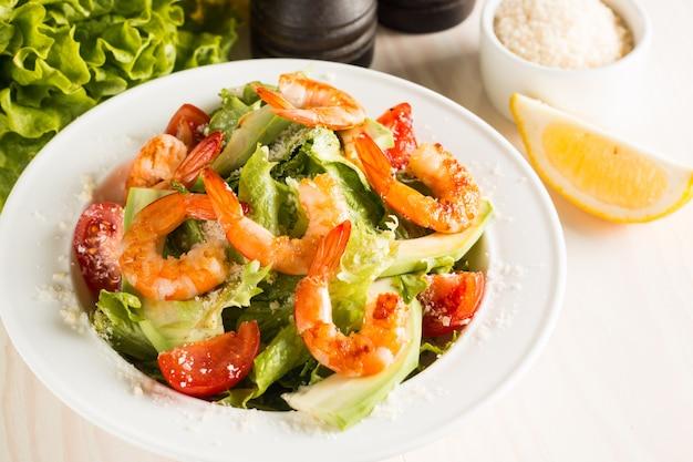 Ensalada de camarones césar fresca con deliciosas gambas, rúcula, espinacas, repollo, rúcula, huevo, queso parmesano y tomate cherry concepto de alimentos saludables y dietéticos.
