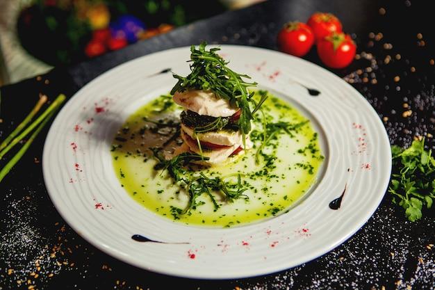 Ensalada caprese en capas con mozzarella, rodajas de tomate y rúcula