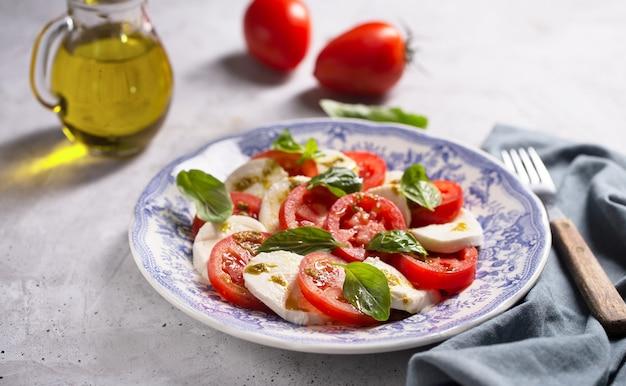 Ensalada caprese. famosa ensalada italiana con tomates frescos, queso mozzarella y albahaca sobre fondo gris