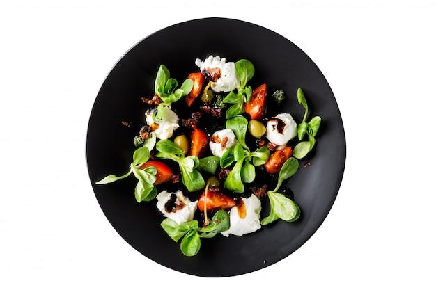 Ensalada caprese italiana fresca con la mozzarella y los tomates en la placa oscura aislada en el fondo blanco.
