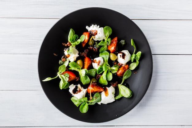 Ensalada caprese italiana fresca con mozzarella y tomates en un plato oscuro en la mesa de madera blanca.