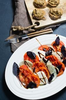 Ensalada caprese italiana. ingredientes queso mozzarella, tomate, albahaca, sal, pimienta, balsámico.