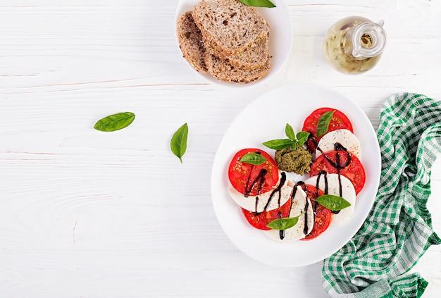 Ensalada caprese italiana tradicional con mozzarella, tomate, albahaca y vinagre balsámico. vista superior, arriba