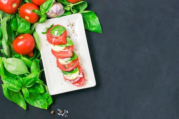 Ensalada caprese con queso mozarella, tomate y albahaca en un plato. fondo negro y espacio de copia