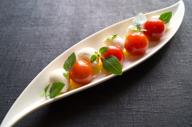 Ensalada caprese con tomates maduros y mozzarella con hojas frescas de albahaca. comida italiana.