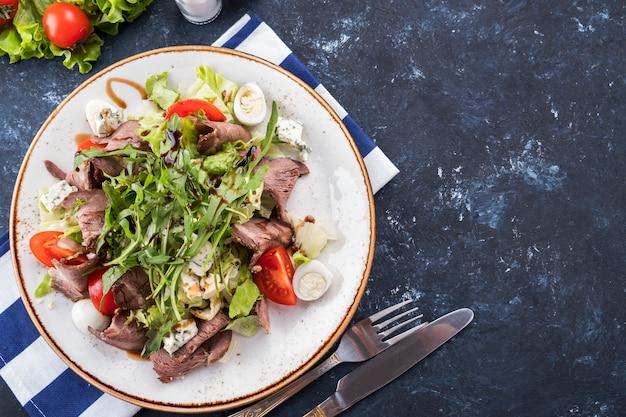 Ensalada de carne asada verduras y queso en un plato. vista superior.