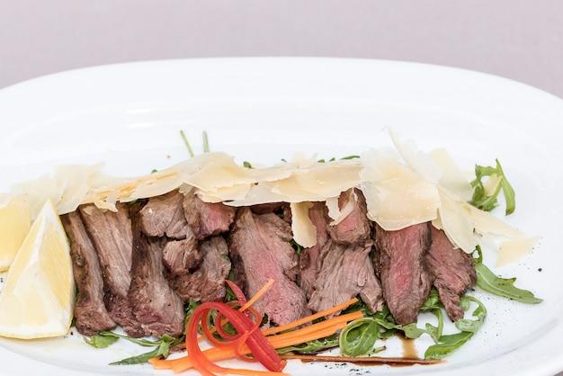 Ensalada de carne a la parrilla, acompañada de parmesano y rúcula.