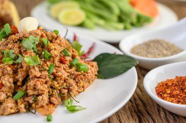 Ensalada de carne picada de cerdo picada en un plato blanco con cebolla roja, hierba de limón, ajo, judías largas, hojas de lima kaffir y cebolla tierna