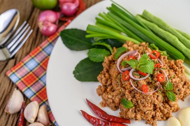 Ensalada de carne picada de cerdo picada en un plato blanco con lentejas, hojas de lima kaffir y cebolletas.