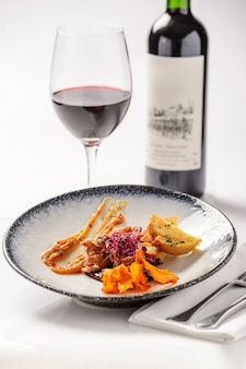 Ensalada de carne, picatostes y batatas con copa de vino tinto